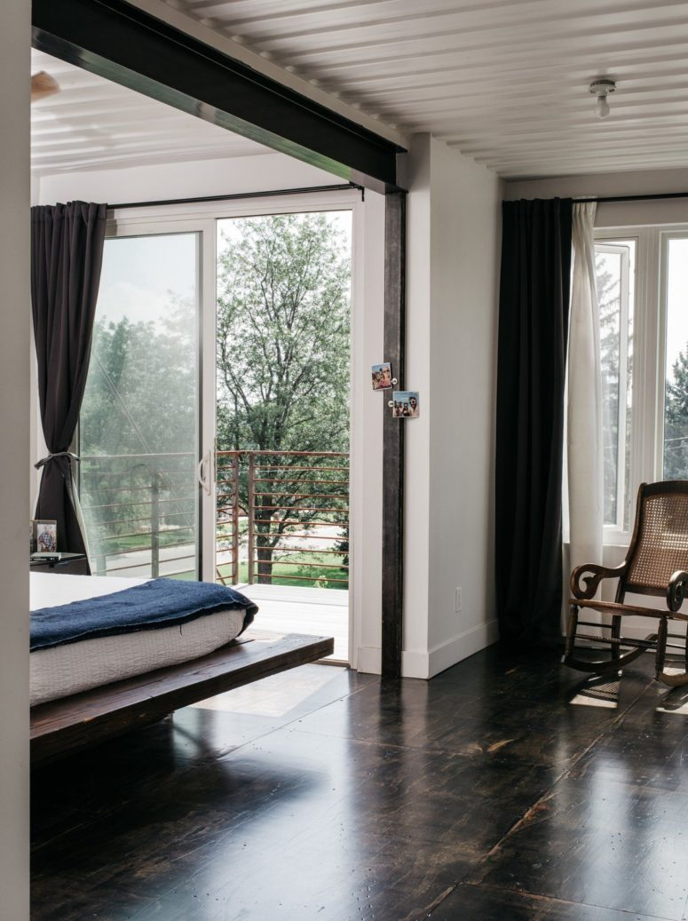 The master bedroom features a platform bed, some chairs, large windows and an entrance to the balcony to enjoy fresh air