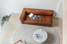 06 The sofa is a chic brown leather couch, which adds texture and chic to the space