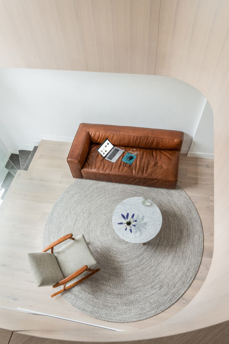 The sofa is a chic brown leather couch, which adds texture and chic to the space