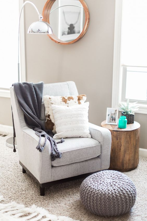 a comfy chair, a knit footrest, a tree stump as a side table, a floor lamp and a round mirror