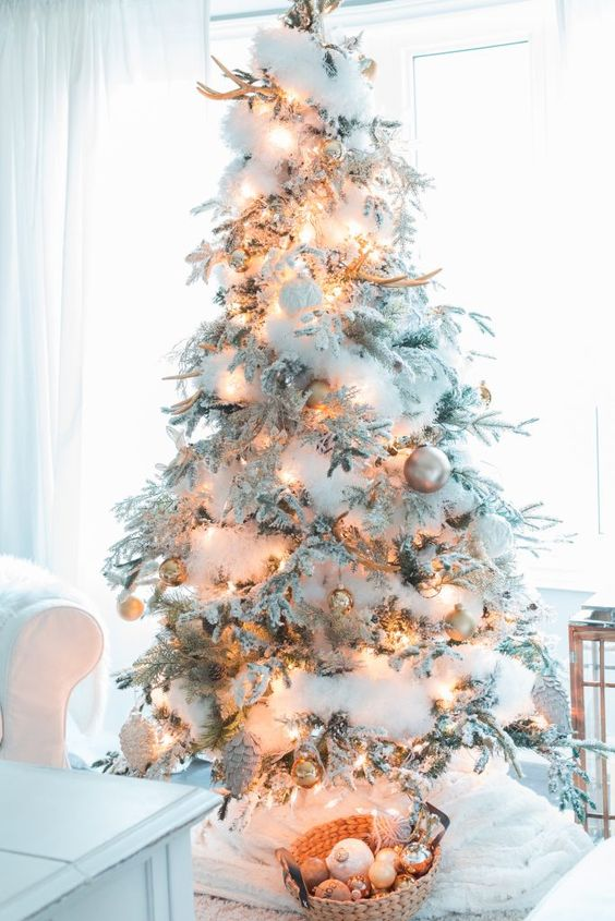 a flocked Christmas tree decorated with cotton to imitate snow, antlers, lights and pinecones and ornaments
