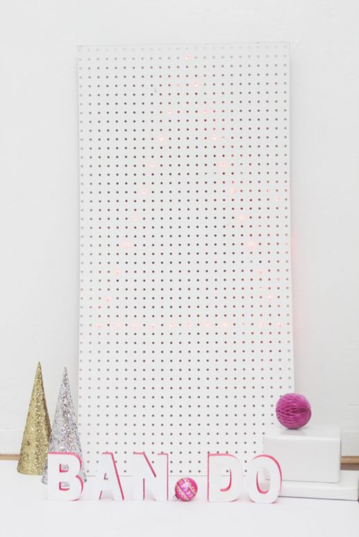 a neon edged Christmas tree on a white pegboard and neon pink letters by the pegboard for a modern whimsy look