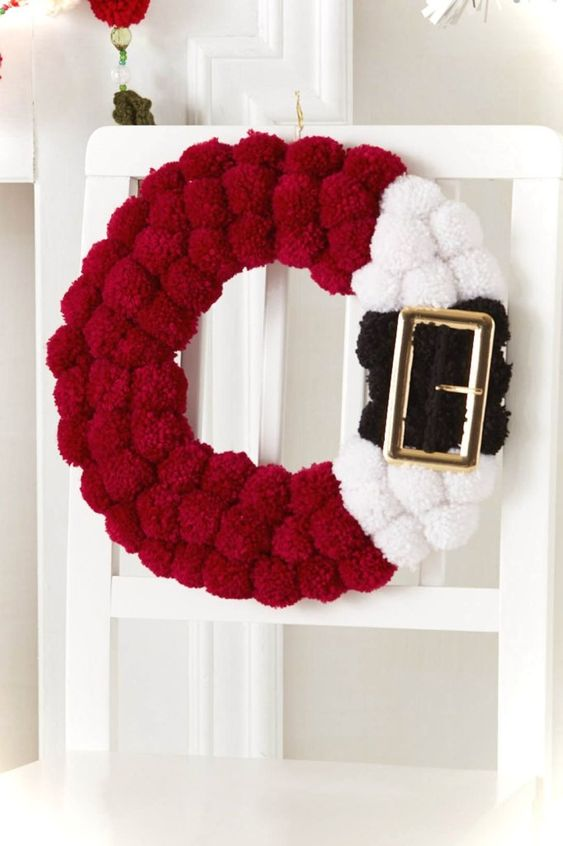 a red, black and white pompom Santa inspired wreath with a large buckle is a fun idea instead of a usual greenery one