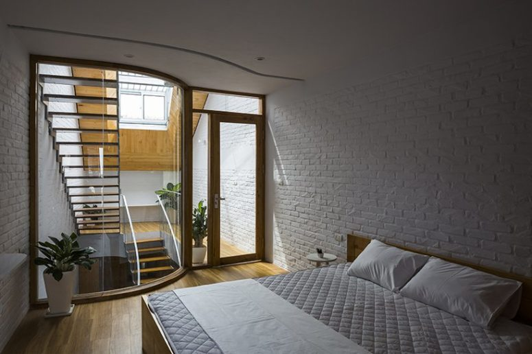 The bedroom is a simple space with a large bed, bedside tables and some plants