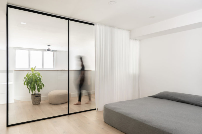 The minimalist bedroom is divided from the rest of the space with glass and there's a large bed