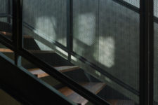 07 The staircase of wood and black metal leads above, to the main living spaces located there