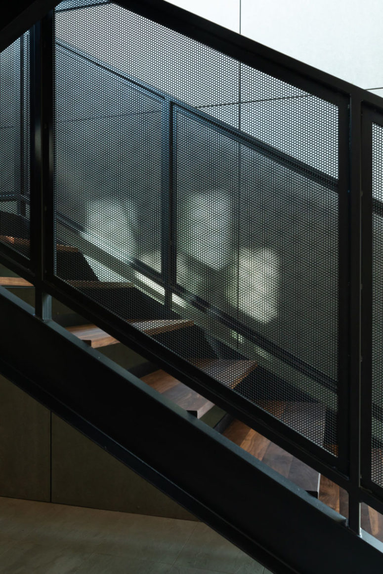 The staircase of wood and black metal leads above, to the main living spaces located there