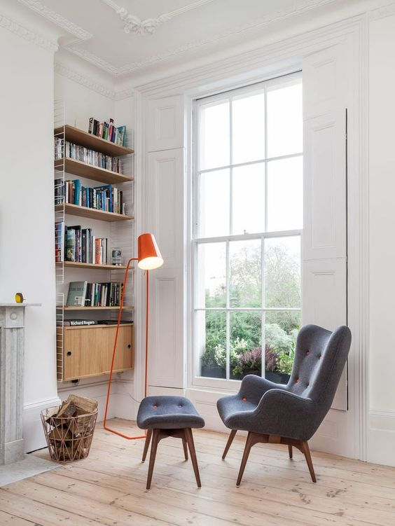 a colorful floor lamp, an upholstered chair with a footrest, a shelving unit on the wall and firewood
