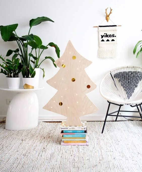a cute plywood Christmas tree decorated withh lights and colorful and metallic stickers on it