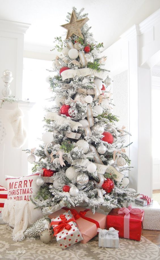 a flocked Christmas tree decorated with white, silver and red ornaments plus ribbons and banners