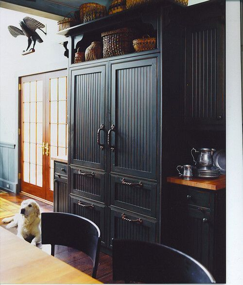 a fridge and freezer integrated into vintage kitchen decor featuring the same doors and handles