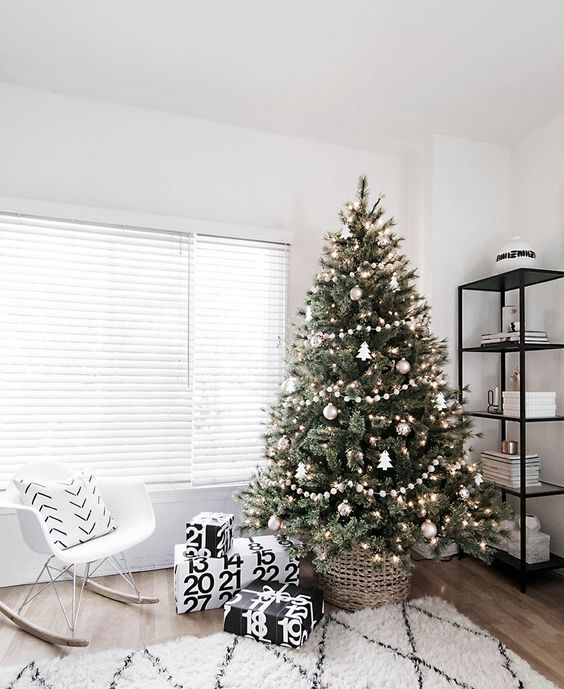 a modern Scandinavian tree with pompom ball garlands, metallic ornaments and tree-shaped ornaments plus lights