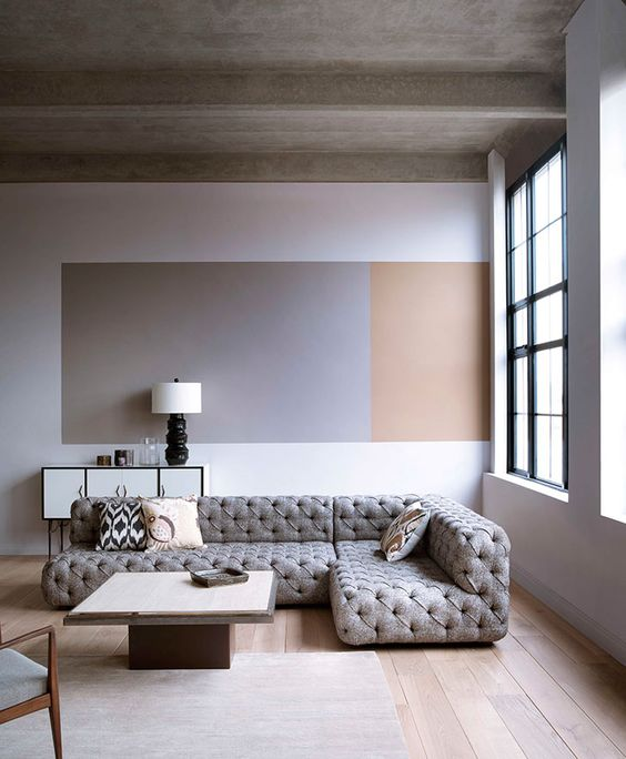 a neutral space done in greys and beige plus warm-colored wood on the floor and an accent on the wall