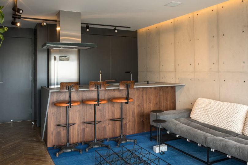 The kitchen is done with sleek black cabinets and a wooden kitchen island with a concrete top