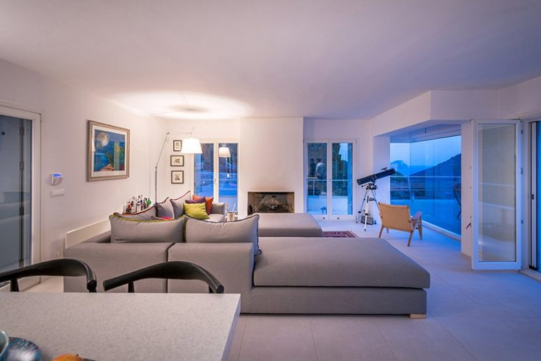 The living room is glazed, with comfy grey furniture, a large fireplace and amazing views