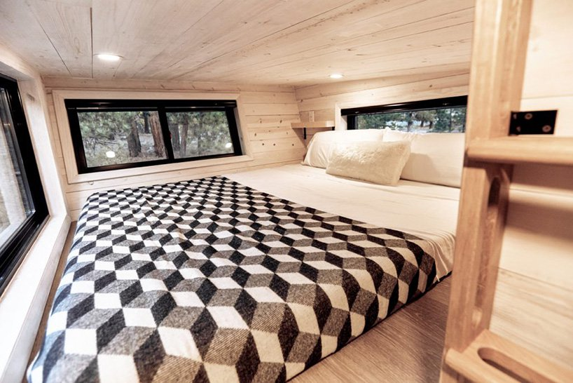 The sleeping space is a small one with a bed right on the floor and windows on each side