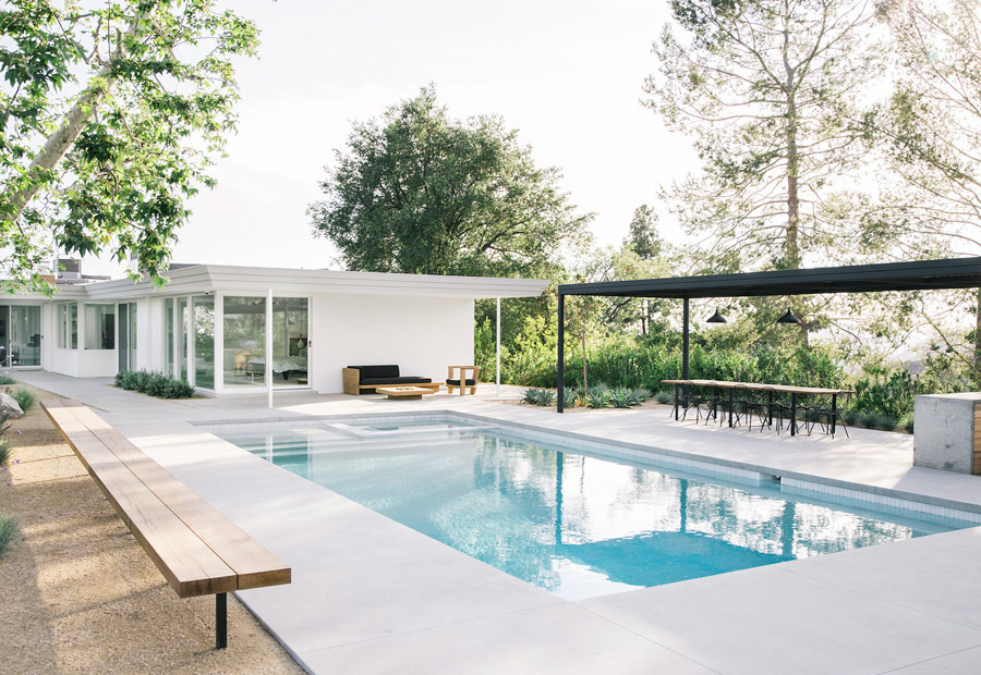 an outdoor area with a pool and a kitchen