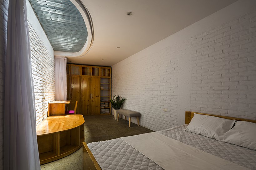 There's another bedroom with a large storage unit, a bench with storage and a curved skylight to illuminate the bedroom