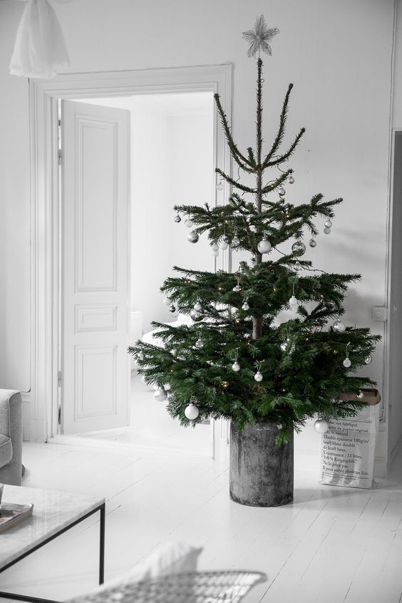 a Nordic Christmas tree with silver and white ornaments in a galvanized bucket is a chic idea for a modern space