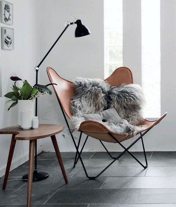a chic modern chair of leather, a wooden side table and a floor lamp that matches the chair frame