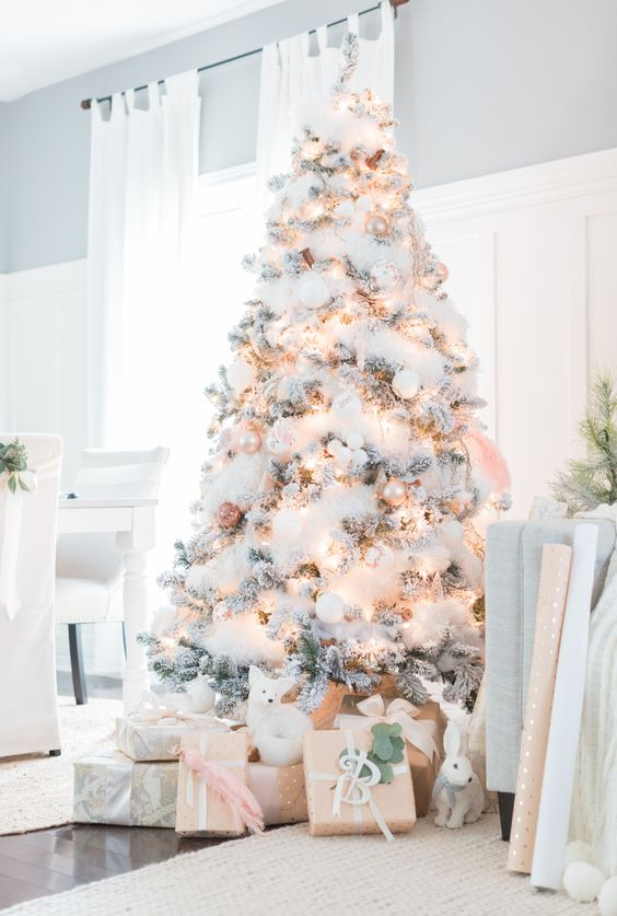a flocked Christmas tree with cotton, lights, white and pearly ornaments plus figurines under
