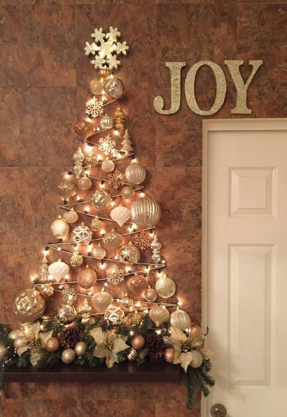 a glam wall-mounted Christmas tree done with lights and white and silver ornaments of various shapes over the mantel