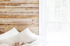 08 a light-filled bedroom with a wood clad wall, neutral linens and a large window