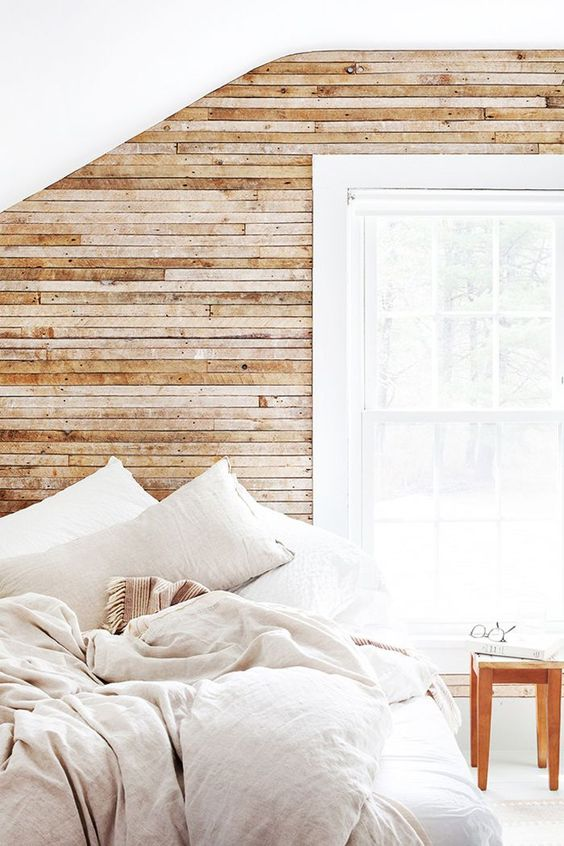 a light-filled bedroom with a wood clad wall, neutral linens and a large window