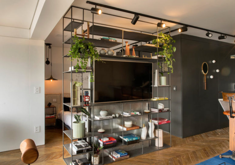 The floor to ceiling shelving unit divides the spaces and hides the sleeping zone