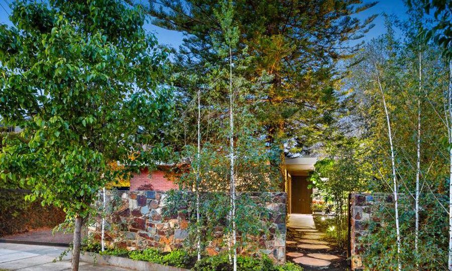 The house is protected with a stone wall and lush greenery to keep it more private