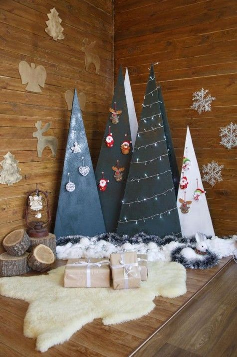a group of plywood Christmas trees in black and white decorated with lights and ornaments hanging on hooks