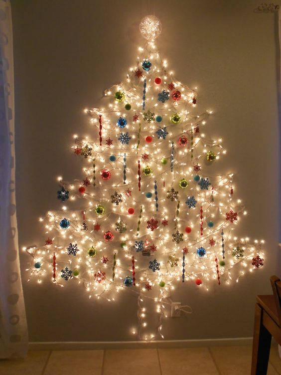 a large Christmas tree on the wlal done of lights and with colorful ornaments all over