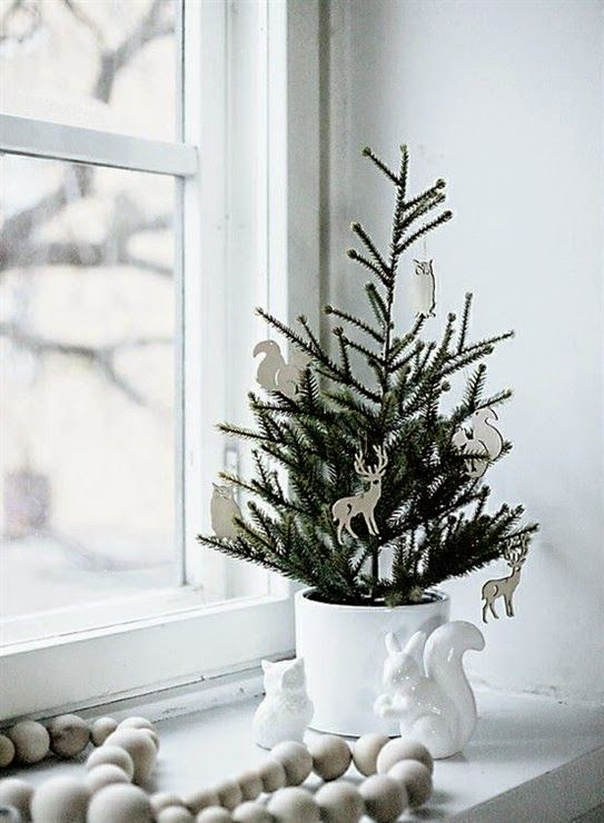 a planted Christmas tree in a white planter and with white plywood laser cut ornaments