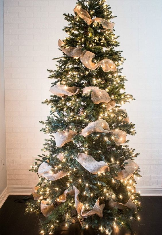 a simple rustic Christmas tree idea with pinecones, burlap ribbons and lights all over   you won't need more