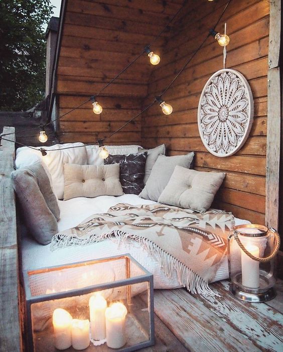 a small and cozy sofa, lots of pillows and throws, large candle lanterns and an oversized dream catcher