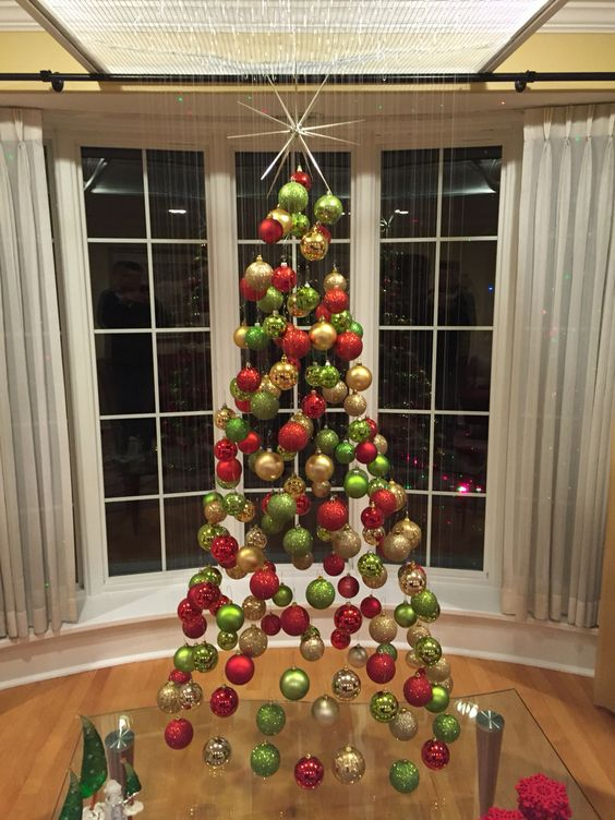 a suspended Christmas tree of ornaments in traditional Christmas colors, green, red and gold is a fun idea