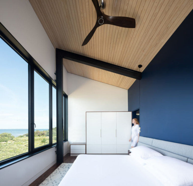 The bedroom is done with a navy statement wall, a glazed wall, an upholstered bed and storage units