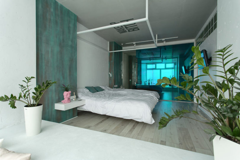 The sliding door is made of emerald glass to match the apartment color scheme