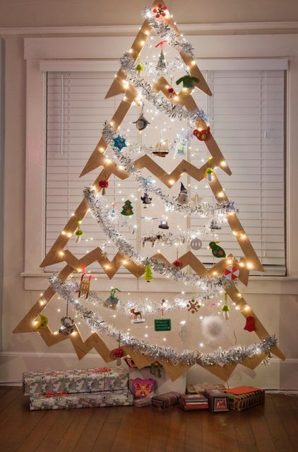 a hanging Christmas tree of plywood decorated with lights, ornaments and garlands for a creative look