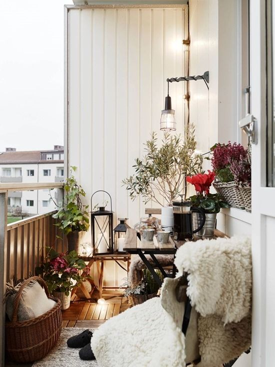 a small space with a chair covered up with faux fur, candle lanterns, baskets and planted flowers