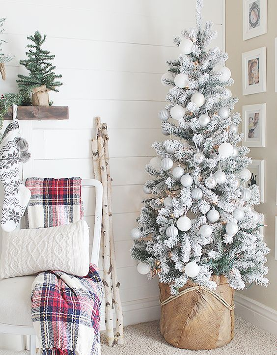 a snowy Christmas tree decorated with pearly, grey and silver ornaments and a base wrapped with burlap