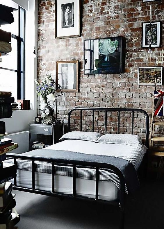 an industrial bedroom with an exposed brick statement wall, which is the centerpiece here