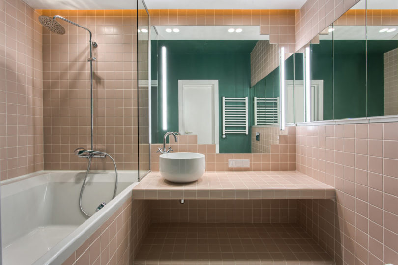 The master bathroom is done in blush and white, wiht a single emerald wall