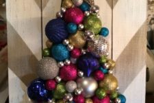 11 a chevron painted board and a colorful and glitter Christmas tree made of ornaments with a star on top