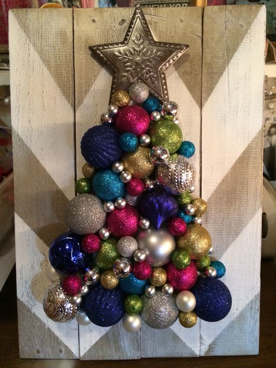 a chevron painted board and a colorful and glitter Christmas tree made of ornaments with a star on top
