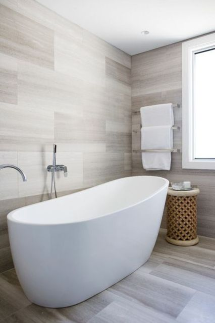 a contemporary bathroom all clad with tiles and with a wooden coffee table   add textures for interest