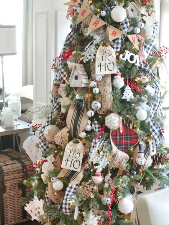a gorgeous rustic meets traditional Christmas tree with jingle bells, burlap ornaments and buntings, plaid ribbons, yarn balls and fake berries
