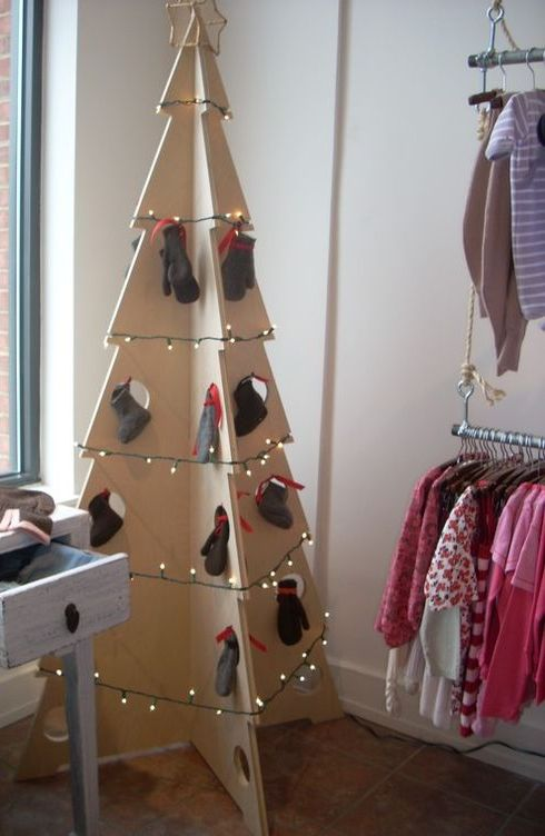 a large plywood Christmas tree decorated with lights and mittens hanging in holes for a simple and modern look