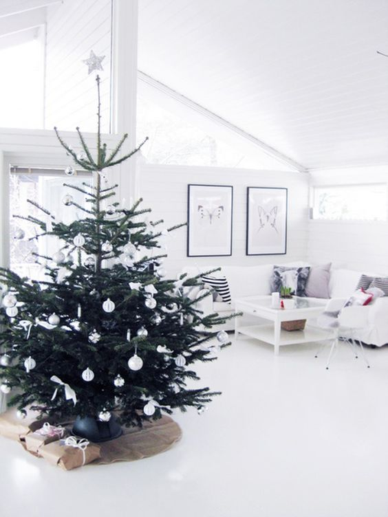 a modern Nordic Christmas tree with white ornaments plus bows and a star on top