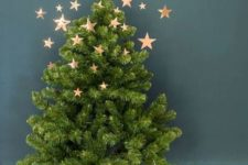 11 a small Christmas tree with burlap on the floor and copper foli stars as decor going up to the wall